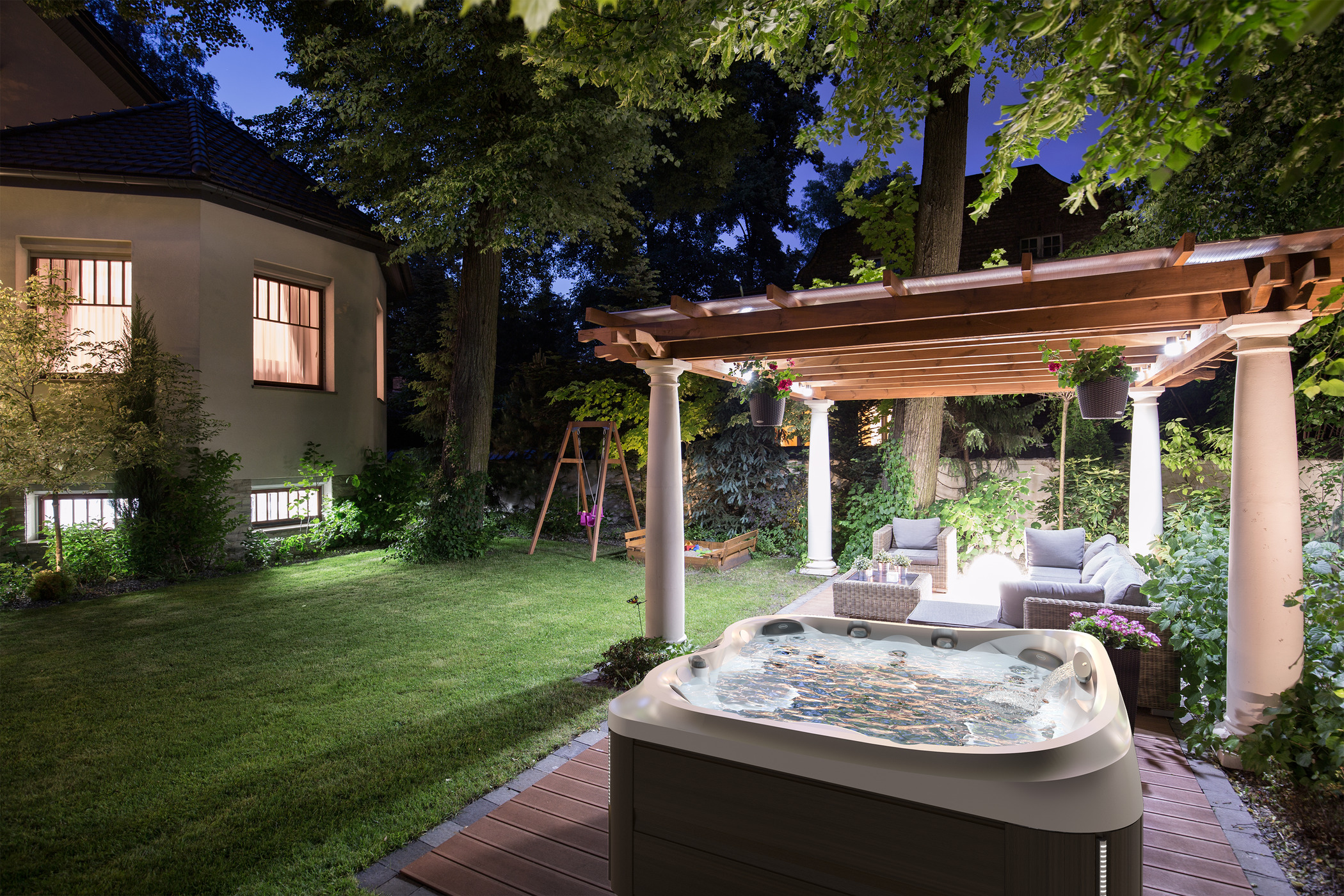Outdoor hot tub installation at night with lights under a pergola.